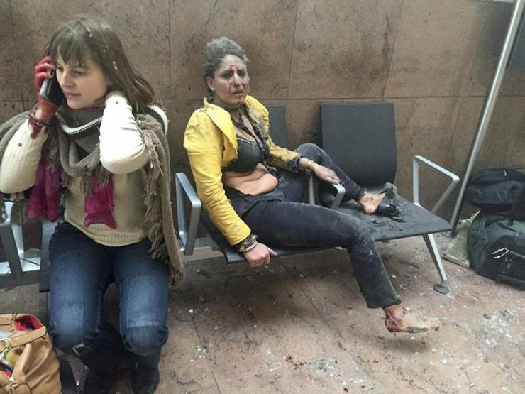 Injured people are seen at the scene of explosions at Zaventem airport near Brussels
