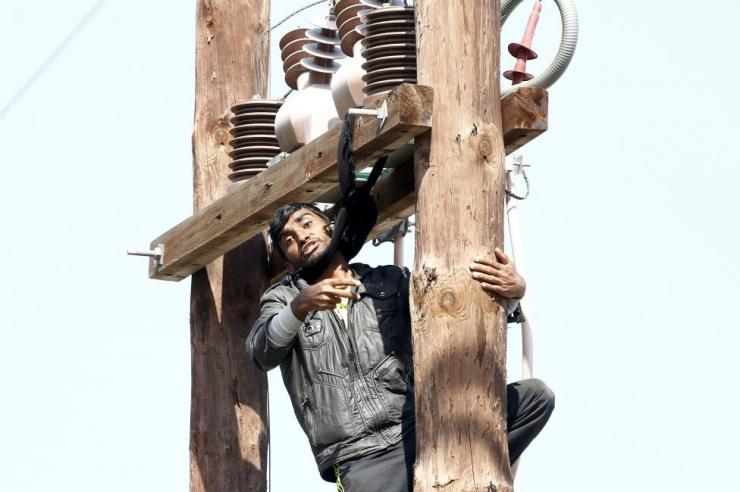 A Pakistani migrant threatens to hang himself from a utility pole during a demonstration inside the Moria registration centre on the Greek island of Lesbos