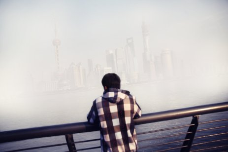 © Souvid Datta. Early on the 1st of January 2014, a man stands on the Bund promenade overlooking Shanghai's futuristic financial district shrouded in a smog of air pollution.