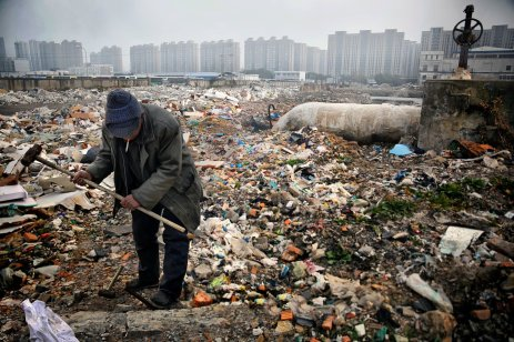 © Souvid Datta. Near the centre of Tianjin in northern coastal China, a man scavenges for scraps of metal at one of the several vast landfill sites used by corporations and small businesses alike. A wastewater pipe is visible, and in the background looms a cluster of new, luxury apartment blocks.