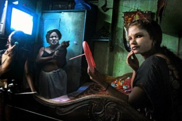 "Datta's photograph, labelled as folows: ""Radhika, 17, in the room of a veteran sex worker, Asma, in Sonagachi (featured dressing in background). The two have grown close over Radhika's period here; she respects and learns from Asma's experience and matter of fact, survival attitude, while Asma feels a fondness for Radhika's unfettered 'kindness, curiosity' and innocence. Strong bonds can often form within brothels as girls learn to support each other and find self-empowerment through group assertion and collective experience."""